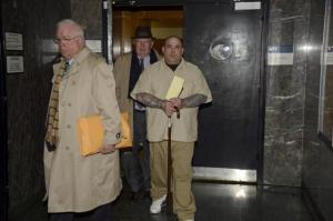 Luigi Grasso (carrying cane), on trial for a gangland murder, is escorted out of Manhattan Supreme Court last month.