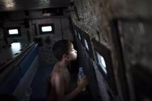 A young resident looks through a small bullet proof window as he sits inside a police armored vehicle after a police operation to occupy the Vila Pinheiro, part of the Mare slum complex in Rio de Janeiro, Brazil, Sunday, March 30, 2014.