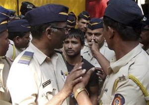 Police officials escort one of the four convicts in a gang rape case to a court in Mumbai, India, Friday, April 4, 2014. An Indian court on Friday sentenced to death three men who raped a photojournalist inside an abandoned textile mill
