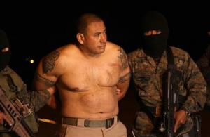 In this photo released by the National Civil Police, masked soldiers escort Jairo Estuardo Orellana in handcuffs after his arrest as they bring him to an air force base in Guatemala City, late Thursday, May 15, 2014. Guatemala's Interior Minister Mauricio Lopez Bonilla announced the government detained Orellana, an alleged member of Mexico's Zetas Cartel drug gan
